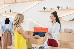 Cashier giving shoe boxes. To woman royalty free stock image