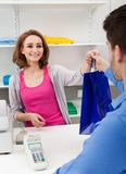 Cashier handing over shopping bag to customer Stock Images
