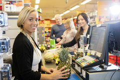 Cashier Holding Pineapple At Checkout Counter In Supermarket. Portrait of smiling female cashier holding pineapple at checkout counter in supermarket Royalty Free Stock Image