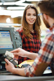 Cashier man on workspace in supermarket shop create payment. Image of cashier men on workspace in supermarket shop create payment with credit card. Focus on lady Royalty Free Stock Photos