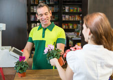 Cashier in retail store serving client Royalty Free Stock Images