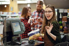 Cashier woman on workspace make okay gesture. Image of cheerful cashier women on workspace in supermarket shop. Looking at camera make okay gesture Stock Photography