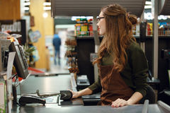 Cashier woman on workspace in supermarket shop. Picture of cashier woman on workspace in supermarket shop. Looking aside Stock Photo