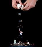 Cashing out. Money pouring out of the broken egg against black background Stock Photo