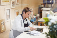 Cashing up for the day. A female deli owner doing her taxes in her shop Royalty Free Stock Image