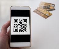 Cashless purchase using qr code and smarphone. Three bank cards Stock Photos