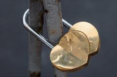 Casier en forme de coeur d'or enchaîné à une barrière en métal Photographie stock