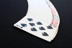 Casinò del poker delle carte da gioco Isolato sul fondo nero della tavola della mazza Immagine Stock