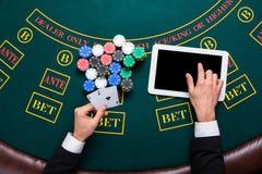 Casinò, gioco d'azzardo online, tecnologia e concetto della gente - vicino su del giocatore di poker con le carte da gioco Fotografie Stock