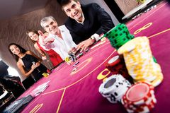 In the casino. Photo of player staking with fashionable people standing near by royalty free stock photos