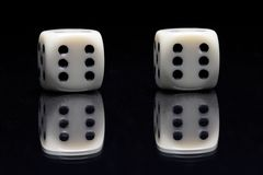 Casino. Ivory play cubes with reflex on black background royalty free stock photos