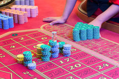 Casino American Roulette gambling table with a playing chips on the layout. Croupier is doing payout Stock Photos