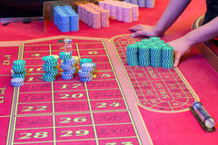 Casino American Roulette gambling table with a playing chips on the layout. Croupier is doing payout Royalty Free Stock Photos