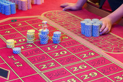 Casino American Roulette gambling table with a playing chips on the layout. Croupier is doing payout Stock Images