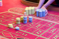 Casino American Roulette gambling table with a playing chips on the layout. Croupier is doing payout Royalty Free Stock Image