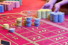 Casino American Roulette gambling table with a playing chips on the layout. Croupier is doing payout Royalty Free Stock Images