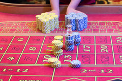 Casino American Roulette gambling table with a playing chips on the layout. Croupier is doing payout Royalty Free Stock Photography