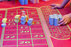 Casino American Roulette gambling table with a playing chips on the layout Stock Photos