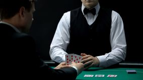Casino businessman client gets bad hand from house croupier, poker gambling. Stock photo royalty free stock photo