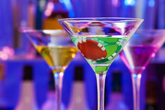 Casino chip in cocktail glasses with bar on back Royalty Free Stock Images