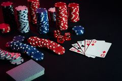 Casino chips and cards on black table surface. Gambling, fortune, game and entertainment concept - close up Royalty Free Stock Images