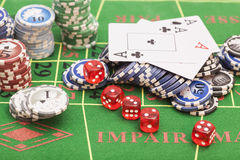 Casino chips, cards and dices. On green felt game table stock photos