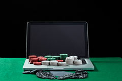 Casino chips and cards on keyboard notebook at green table. Royalty Free Stock Images