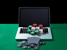 Casino chips and cards on keyboard notebook at green table. Royalty Free Stock Photo