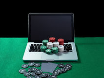 Casino chips and cards on keyboard notebook at green table. Stock Photos