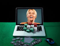 Casino chips and cards on keyboard notebook at green table. Stock Image