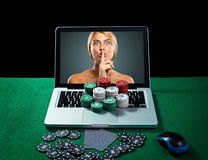 Casino chips and cards on keyboard notebook at green table. Royalty Free Stock Photos