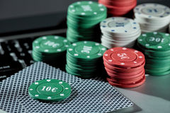 Casino chips and cards on laptop to play gambling online. Stock Image
