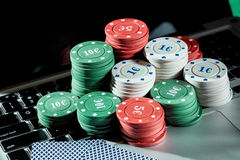 Casino chips and cards on laptop to play gambling online. Stock Photos