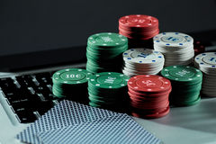 Casino chips and cards on laptop to play gambling online. Royalty Free Stock Images