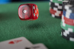 Casino chips, cards and red dices on green felt game table Royalty Free Stock Images