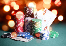 Casino chips and cards, two aces on the playing green table against bright bokeh lights. Poker game theme backdrop Stock Photography