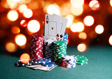 Casino chips and cards, two aces on the playing green table against bright bokeh lights. Poker game theme backdrop Stock Image