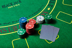 Casino chips and deck of cards lying on casino table Royalty Free Stock Image