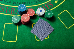 Casino chips and deck of cards lying on casino table Stock Images