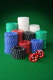 Casino chips and dice. Stacks of casino chips and dice on green felt Stock Photography