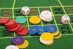 Casino chips and dices stacking on a green felt Royalty Free Stock Image