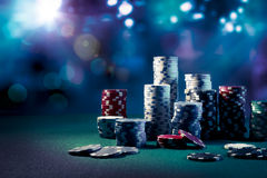 Casino chips with dramatic lighting and lens flares Royalty Free Stock Photography