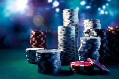 Casino chips with dramatic lighting and lens flares Royalty Free Stock Photos