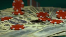 Casino chips falling on dollar bills, big winnings, jack-pot, slow-motion. Stock footage stock video