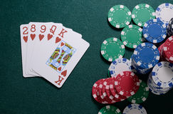 Casino chips and flush cards combination on the green table. Poker game concept Royalty Free Stock Photo