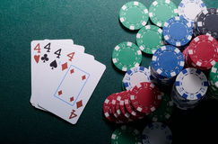 Casino chips and four of kind cards combination on the green table. Poker game concept Royalty Free Stock Image
