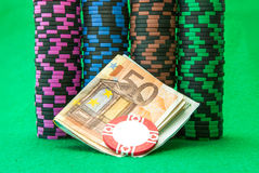 Casino chips on green table with Euro Stock Images
