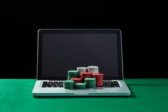 Casino chips on keyboard notebook at green table. Stock Photo