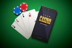 Casino chips and mobile  on green background Royalty Free Stock Photography