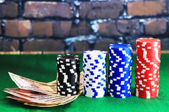 Casino chips and money on green poker table Royalty Free Stock Images
